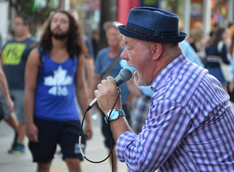 singer Johnny Max sings at a street festival, blue fedora, purple check shirt, a man in the background with a 416 Toronto T-shirt on