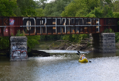 a yellow kayak with two people in it passes under an old railway bridge that has graffiti on it. Don River