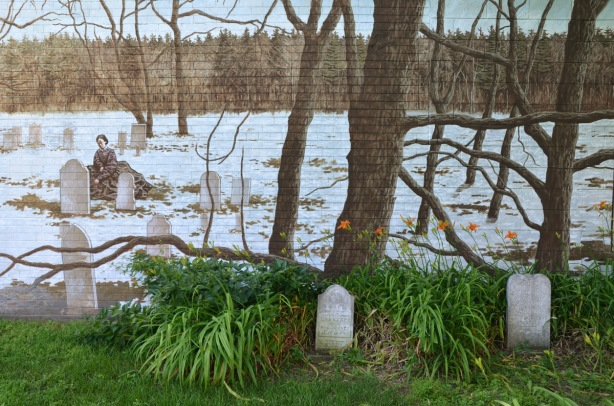 two real but old and weathered tombstones in a cemetery, with a mural of trees in winter around a cemetery where a woman sits by a grave