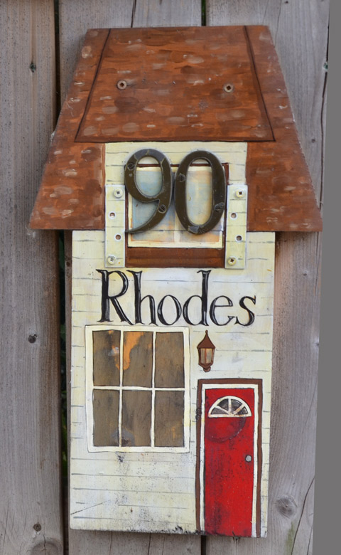 wooden plaque ornament on a wood fence, shape of a house with large window and little red door