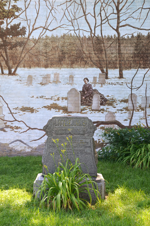 a real tombstone, surname Littlejohns, in a cemetery, with a mural in the background showing a woman kneeling by a grave in the winter, small amount of snow, no leaves on the trees