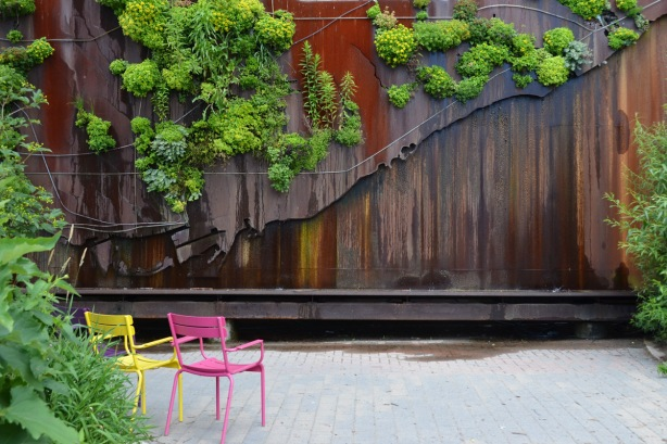 a pink chair and a yellow chair sit in front of a sculpture that is a metal relief map of Toronto, green plants grow in the areas of the map that are ravines and green spaces in the city