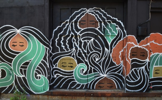 mural, black background with faces with eyes closed and flowing stylized hair