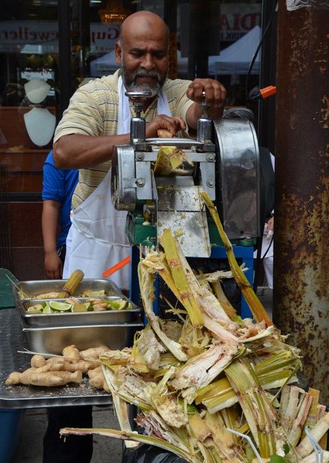 a man shreds sugar cane in a machine to extract the sugar cane juice which he is then selling, outside, street festival, Little India