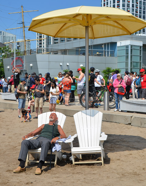 an older man is sleeping on a white muskoka chair and under a big yellow umbrella at HTO beach in Toronto, crowd of people standing behind him