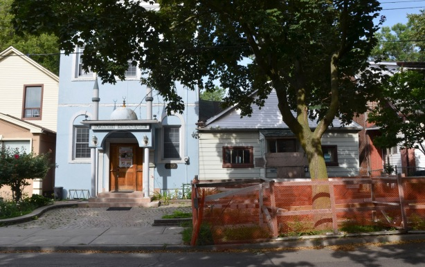 looking across a street, sidewalk, large tree with orange plastic fence around it to protect it during construction, a pale blue building that is a mosque and a small single storey house that is about to be demolished.