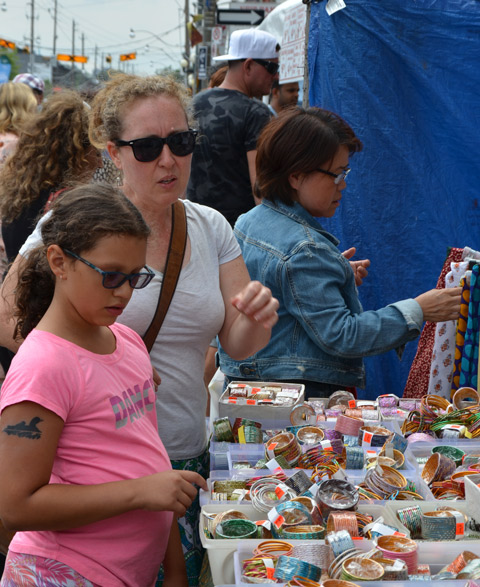 mother and daughter look at bangles, jewellery, for sale outside, at street festival. Both are wearing sunglasses