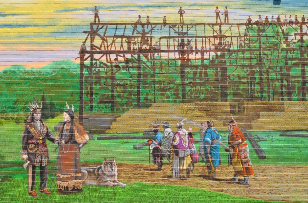 part of a larger mural showing the story of Port Union - two brick buildings, houses, a group of women sitting outside with baskets on the ground, a vintage car