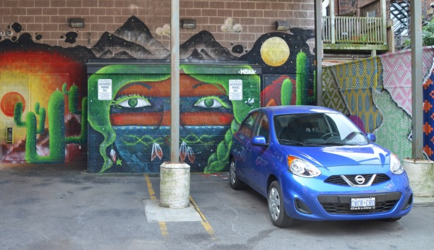 a blue car is parked in front of a mural of a face with desert symbolism, a large cactus is in the mural beside the face
