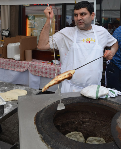 a man removes freshly baked naan from a tandoori oven