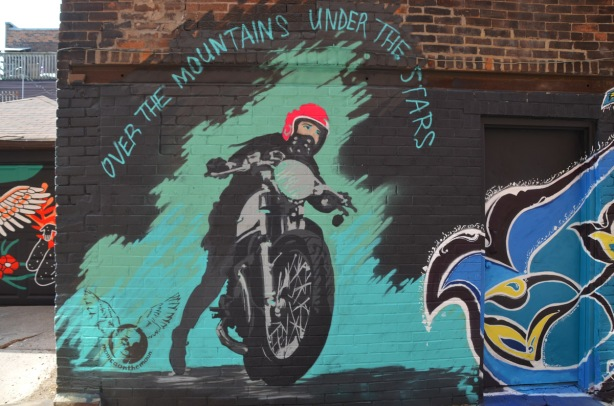 a monica on the moon mural with a woman getting on a motorcycle in grey tones except for the helmet which is red. the words Over the Mountains and under the stars are written over the motorcycle