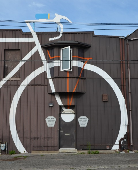 side entrance to a large brown building (a bike shop) that has a large white line drawing of a bike on it. The door is in the middle of the front wheel. A structure that looks like the handlebars of the bike is on the roof