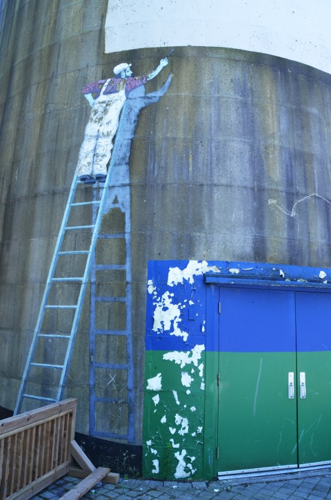 painting on a cylindrical building, of a man on a ladder, painting, also his shadow