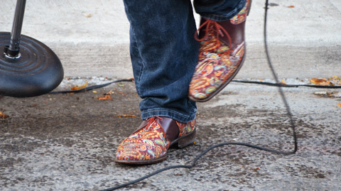 shoes of a man who is moving as he sings, street and sidewalk in the photo