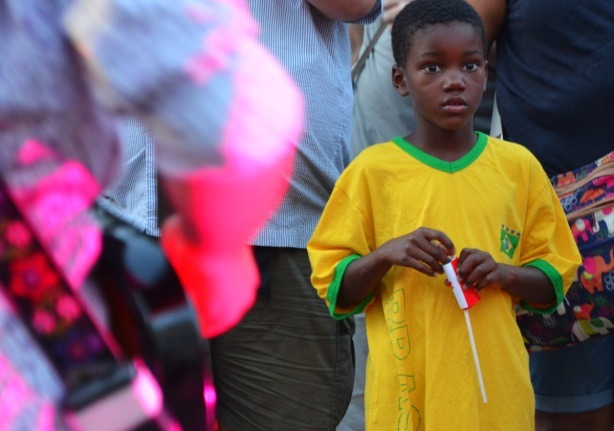 a young boy in a large yellow T-shirt is watching musicians outdoors.