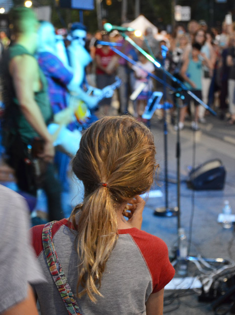 back of a girls head, long hair tied in a ponytail, outside, in the evening, as she watches a music performance with a small crowd of people