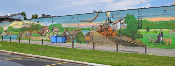 left side of a large mural showing the history of Port Union, first nations, first white settlers, up to the early 1900s