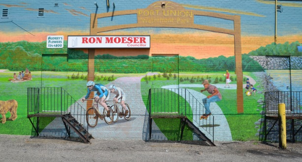 part of a larger mural showing the story of Port Union - this time, the Port Union waterfront park is featured, cyclists on the bike path, a skateboarder, people enjoying the park, 3 entrances to the backs of stores, including Audreys flowers and Councillor Ron Moeser's office. a