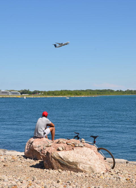 a man in a red baseball cap sits on a rock, his bike parked beside, while watching a pOrter airlines plane take off from Billy Bishop Airport