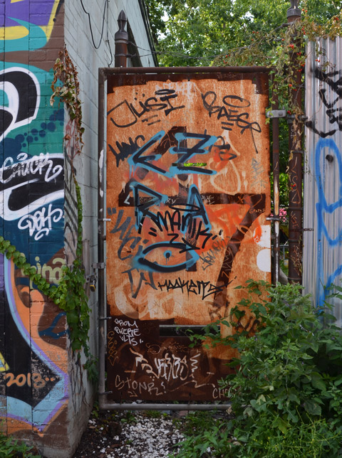 metal gate that has rusted. large numeral 47 on it as well as some graffiti scrawls