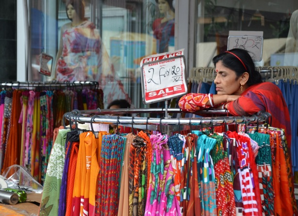 a woman leans on the top of a rack of clothing for sale, sidewalk sale, as part of the South Asian Festival on the Gerrard Street.