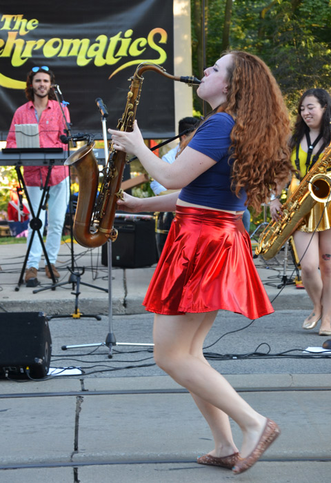 a woman in a red skirt plays the saxophone on the street, a part of the Achromatics, a music group, a man on keyboards stands in the background