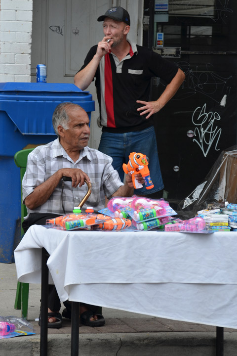 an older man sits behind a small table covered with a white cloth. on the table are toys that he is selling. he is holding an orange Nemo shaped bubble maker plastic toy. behind him, a man is standing smoking a cigarette