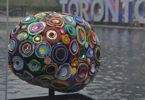a brain sculpture on display in front of the 3D toronto sign, decorated with colourful circles of sequins