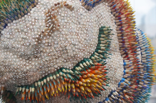 a sculpture of a brain decorated with hundreds of coloured pencils, some are point up and some are blunt end up, the colours of the pencils make shapes and lines on the brain