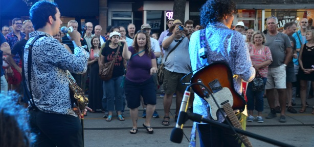 two musicians with lights on them, from the back, with the crowd standing on the street in front of them, one woman dancing