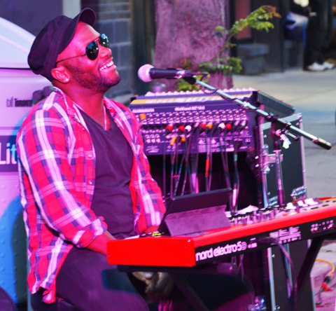 a youngblack man in sunglasses and black hat sits at a keyboard with mircophone in front of him, evening, some red lights are shining on him. outside.
