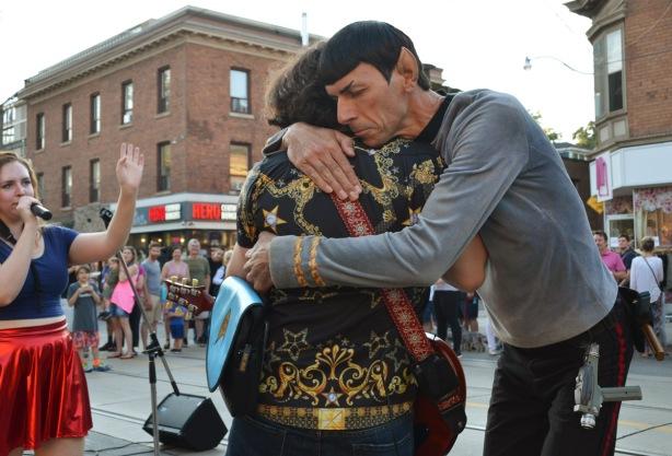 a man dressed as Dr. Spock from Star Trek hugs a musician at an outdoor music festival
