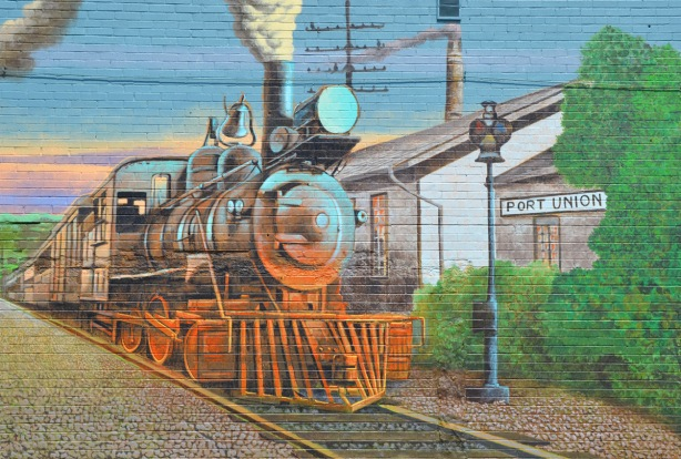 part of a larger mural showing the story of Port Union - a steam engine pulls a train into the station