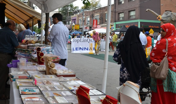 street scene at South Asian festival. a man hits a ball with a cricket bat, two women in head scarves are talking, men behind a table are selling jewellery and clothes