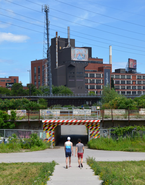two men walk through a park towards an underpass under a railway track, factory in the background.