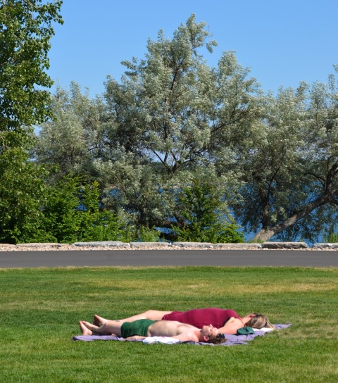 two people lying on a blanket on a grassy area in a park, trees in the background