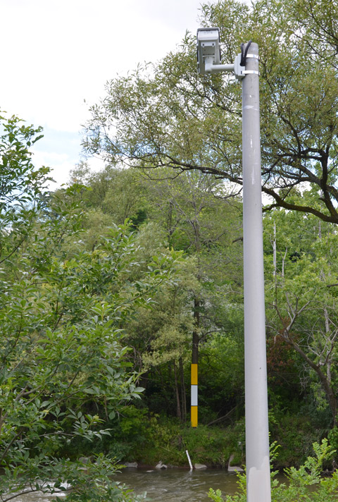 surveillance camera on a tall pole, aimed at rulers and markers on the far side of a river, keeping an eye on the water level