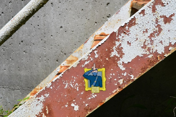 a urban ninja squadron sticker on the side of a metal staircase that was painted brown but the paint is peeling off