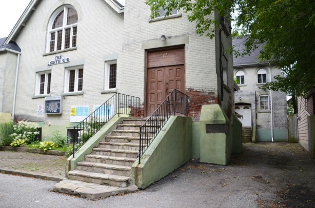 steps up to a large brown door, one of the entrances of the Toronto Gospel Lighthouse church, a greyish white building with another building behind.