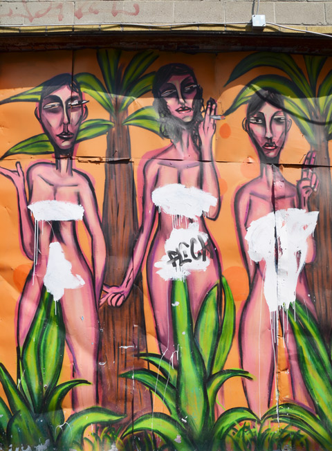 street art mural of three naked women. Someone has painted white over the private parts