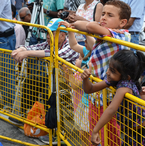 young kids lean over a yellow barricade as they watch a performance a girl is giving a thumbs up sign