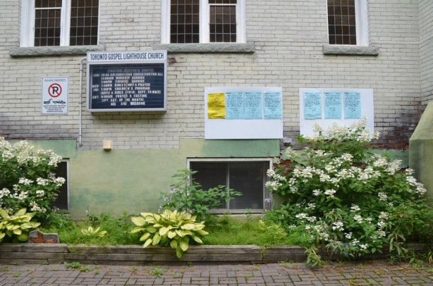 exterlior side wall of the Gospel Lighthouse church, small garden in ront with shrubs and hostas, also blue notices tacked to the wall, re application for variances to the zoning code.