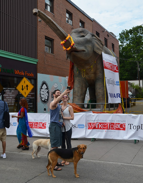 a couple, man and woman, each with a dog on a leash, is taking a selfie in front of a large elephant sculpture