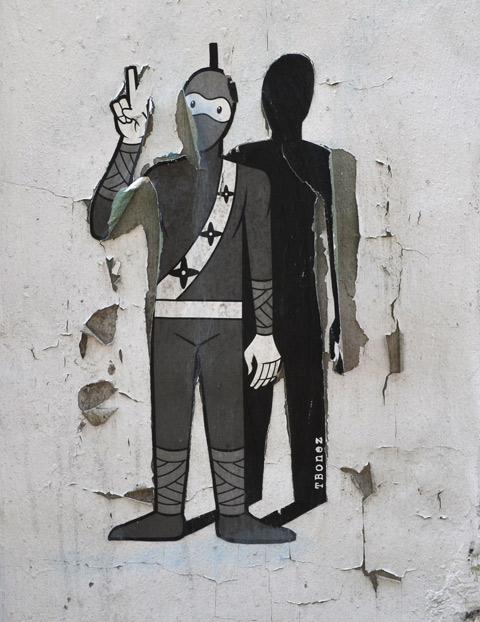 a tbonez urban ninja squadron pasteup - standing with hand up and fingers crossed, has a shadow