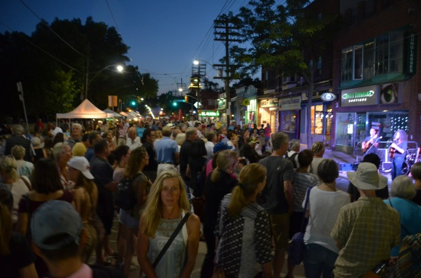 evening, darkening sky, many people on the street at a street festival, most people are facing away from the camera except one woman in front who is looking straight ahead. Musicians playing on the right, standing in front of stores