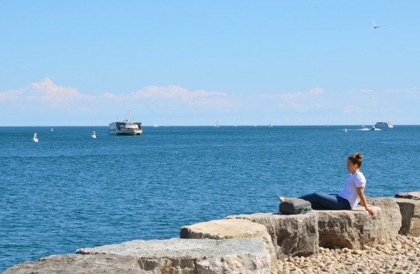 a woman sits on a rock wall, looking out over Lake ontario, there are boats on the water and a sea gull flying past