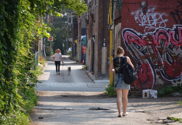 a woman walking her dog in an alley, another woman walking away from the camera