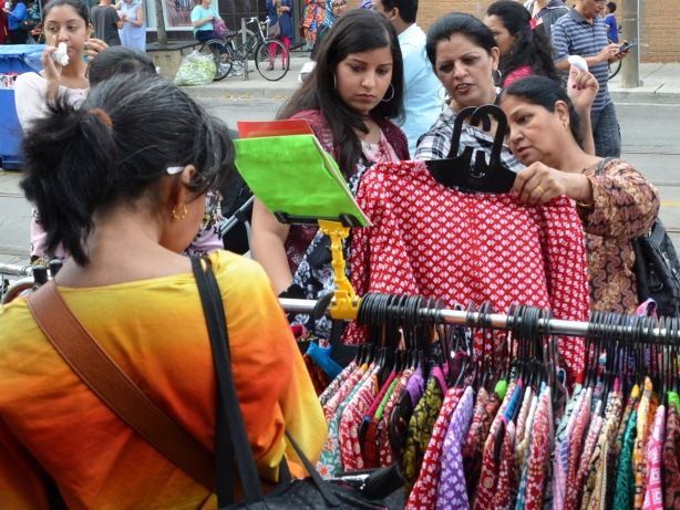 three women are looking at a blouse (dress?), red and white pattern, on a hanger at an outdoor sidewalk sale, as part of a street festival. They are looking at the same piece of clothing