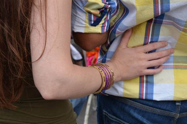 a woman with shiny bangles, bracelets, on her wrist puts her hand on her boyfriend's lower back