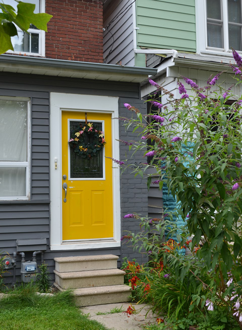 yellow front door on a greyhouse, with lots of flowers in front including purple butterfly bush